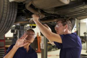 Ausbilder und Schueler reparieren ein Auto