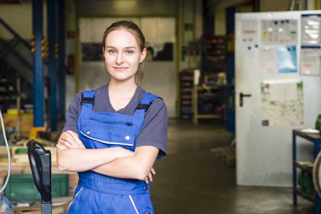 Junge Auszubildene zur Metallerin in Arbeitskleidung
